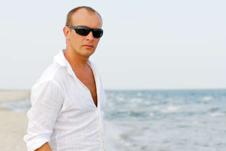 side pose: Portrait of handsome man relaxing by sea wearing sunglasses.