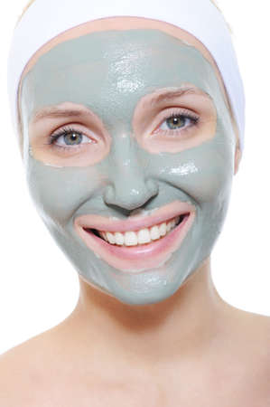 cosmetic mask of clay on the young smiley female face - white background