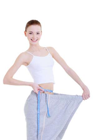 pretty young beautiful girl measuring her thin waist photo