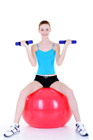 physical exercises with dumbbells and fitball for young woman - isolated photo