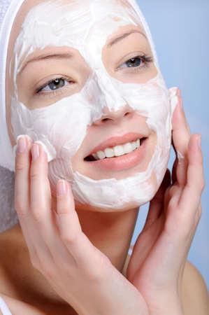 pulizia viso: close-up giovani donne devono affrontare nella maschera cosmetici - colore di sfondo