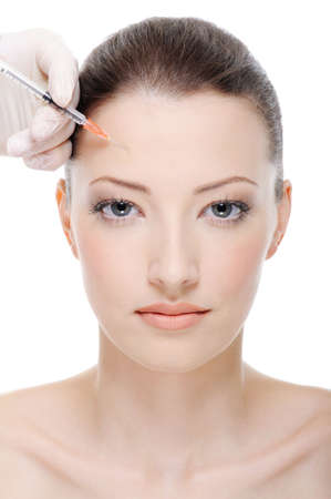injection of botox on female forehead - female portrait photo