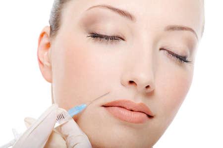 cheek to cheek: botox shot in the female cheek - female  face close-up