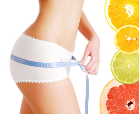 cellulite: Woman measuring perfect body - after dieting on citrus fruits
