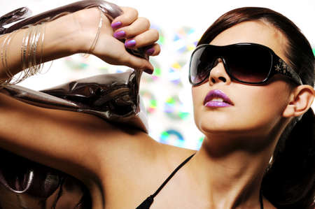 bright beautiful young woman with fashion sunglasses and handbag photo