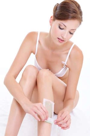 Pretty woman doing depilation on her legs with waxing - isolated photo