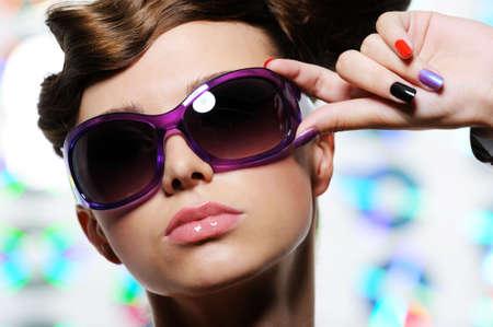 female face closeup: fashion stylish sunglasses on the beautiful female face - close-up Stock Photo