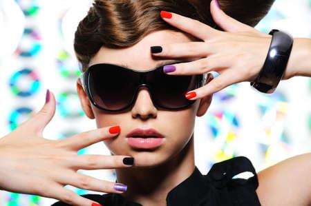 feminity: adult woman with fashion multicolored manicure and female stylish sunglasses - close-up