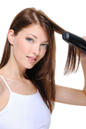 Portrait of young beautiful girl doing hairstyle with hair iron photo