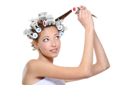 curling: curling of hair by the young beautiful woman - white background