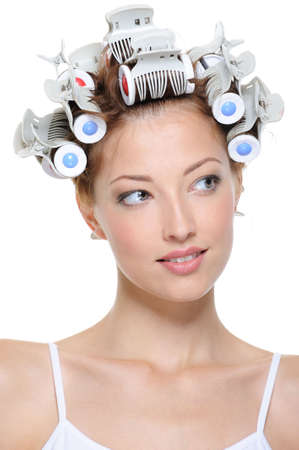stilist: Portrait of beautiful young smiling female with curlers - close-up