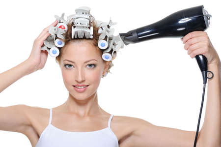 hairdryer: young woman with hair-curles and hairdryer doing hairstyle - isolated on white Stock Photo