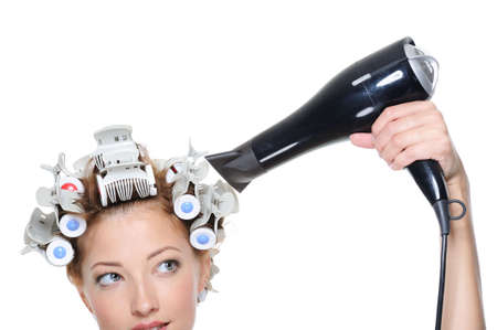 female with black hairdryer drying female head in hair-curled - close-up photo