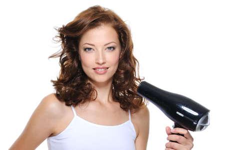 tratamiento capilar: retrato de la joven y bella mujer con el peinado de moda la celebraci�n de secador de pelo Foto de archivo