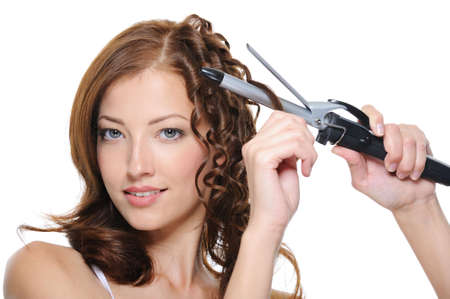 curling: curling female brunette hair with roller - beautiful woman portrait Stock Photo