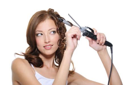 ringlet: beautiful woman curling her brunette hair with roller - isolated  Stock Photo