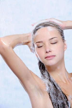 versoepeling van de jonge vrouw nemen douche - close-up portret