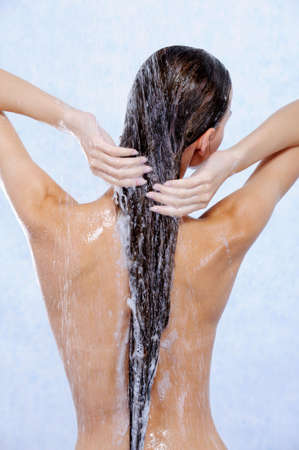 woman in shower: young woman taking shower and washing her hair - back view