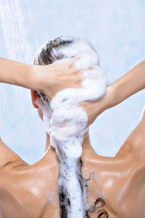 shampooing: washing long brunette female hair by shampoo - close-up