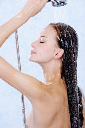 Profile of young beautiful woman washing her long hair photo