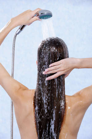 douche: Female holding douche and washing hair - back view