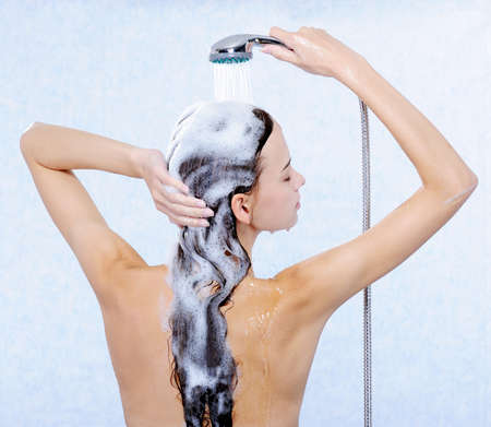 washing hair: Pretty female standing back and washing her long hair Stock Photo