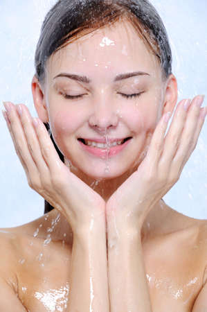 splashes and drops of water on the happy young female face photo