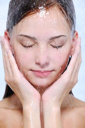 mojado: Flujos de agua en la joven hermosa cara femenina - close-up