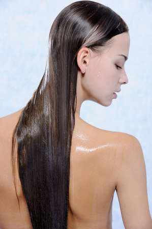 Back view of pretty young female with wet long hairs photo