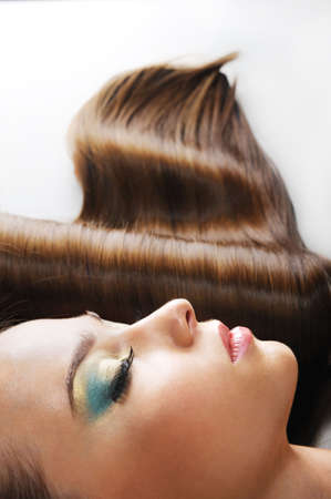 close-up portrait of beautiful young woman with closed eyes and health gloss hairs photo