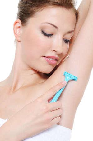 armpit: Aplicando la navaja de afeitar axila por hermosa joven