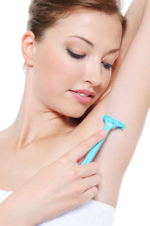 Applying razor to the shaving armpit by beautiful young girl photo