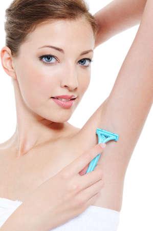 axilla: Pretty woman shaving armpit with razor - close-up portrait  Stock Photo