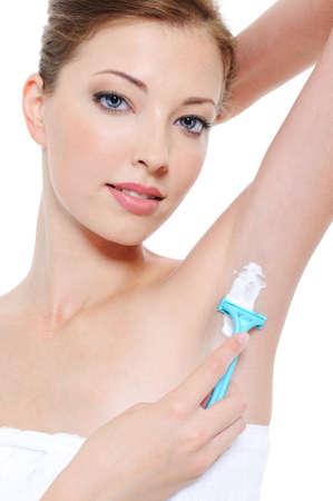 armpit: Portrait of pretty young woman shaving underarm with razor  Stock Photo