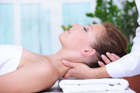 adult massage: Neck massage for young woman relaxing in spa salon  Stock Photo