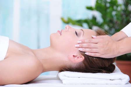 face massage: Beautiful woman in the beauty salon getting a face massage