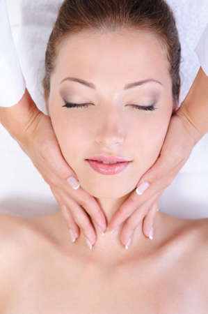 pretty woman face: Hands of beautician giving pretty woman face massage Stock Photo