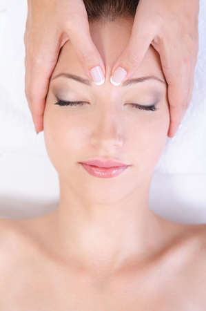 hand on forehead: Face massage for young woman in spa salon - close-up