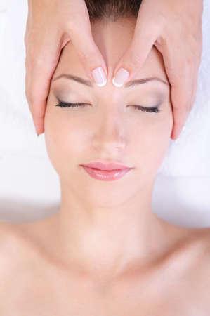 Masaż twarzy dla młodej kobiety w salon spa - Close-up