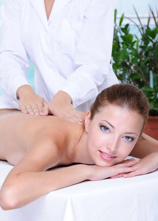Cheerful face of pretty woman getting back massage Stock Photo - 5248947