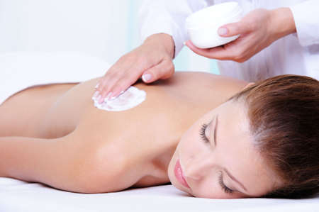 back rub: Applying moisturizing cream on the female back before massage - close-up