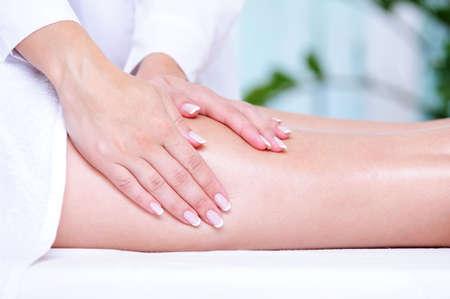 piernas mujer: Beautician las manos haciendo masajes para la pierna femenina - close-up
