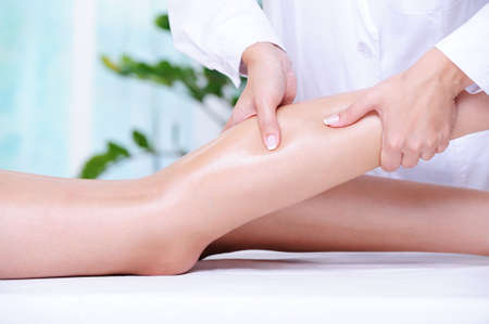 therapeutic massage: Therapeutic massage for the female beautiful leg by beautician in the spa salon