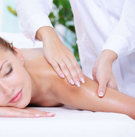 relaxation massage: Beautiful calm woman getting massage of shoulder in the beauty salon