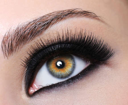 pesta�as postizas: Mujeres con los ojos brillantes negro de maquillaje y pesta�as largas Foto de archivo
