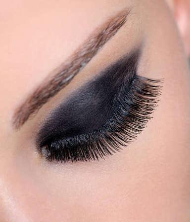 pesta�as postizas: Cerrado humano femenino con los ojos brillantes y sombra de ojos negro largo pesta�as falsas Foto de archivo