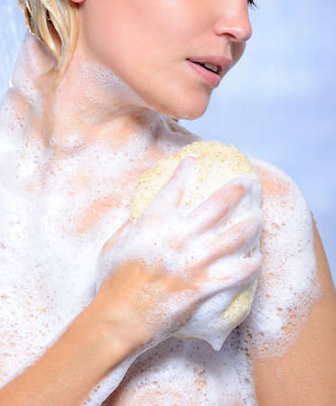 soap suds: Young woman pampering her body with sponge and soap suds
