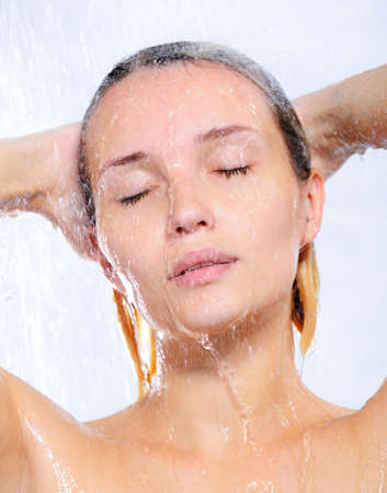 Portrait of beautiful pretty young woman taking shower photo