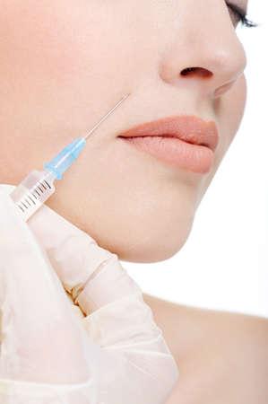 zastrzyk: Lekarz robi botox zastrzelony kobiet policzek - fragment twarzy