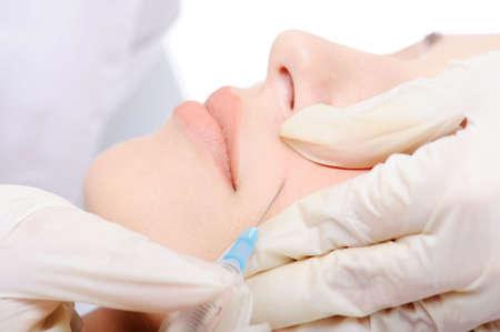 Schoonheidsspecialist toepassing van botox schot in de wang van jonge vrouw
